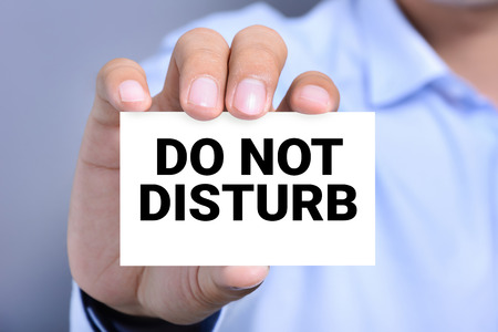 do not disturb: DO NOT DISTURB, message on the card shown by a man Stock Photo
