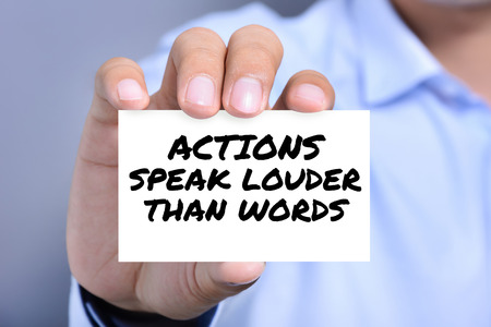 louder: ACTIONS SPEAK LOUDER THAN WORDS, message on the card shown by a man