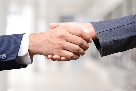 acquisition: Handshake of businessman and businesswoman - greeting, dealing, merger and acquisition concepts Stock Photo