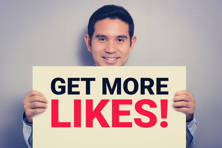 likes: GET MORE LIKES!, message on white cardboard held by smiling man, vintage tone
