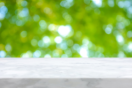 White marble stone countertop on natural fresh green bokeh abstract background - can be used for display or montage your products