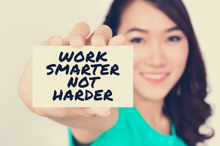 harder: WORK SMARTER NOT HARDER, message on the card shown by a woman, vintage tone