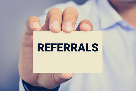 referral marketing: REFERRALS word on business card shown by a man, vintage tone