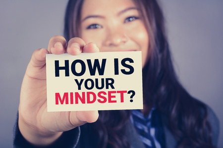how: HOW IS YOUR MINDSET? message on the card shown by a woman, vintage tone