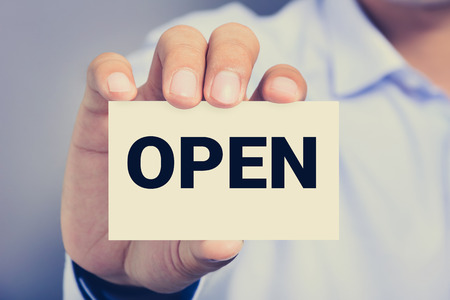 open sign: OPEN sign shown by a man Stock Photo