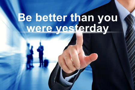 yesterday: Businessman hand touching Be better than you were yesterday motivational message on virtual screen