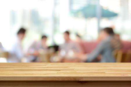 Piano tavolo in legno su sfocatura sfondo di persone in caffetteria - può essere utilizzato per la visualizzazione o il montaggio dei vostri prodotti
