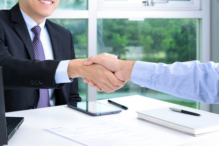 deal: Handshake of businessmen in the office - making an agreement and dealing concepts Stock Photo