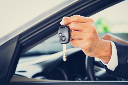 Mano que sostiene una llave del coche - concepto de venta de los vehículos y el negocio de alquiler, el tono de la vendimia