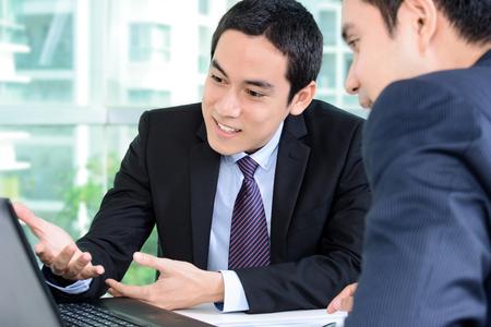 reuniones empresariales: Los hombres de negocios que discuten el trabajo mientras busca en la computadora portátil