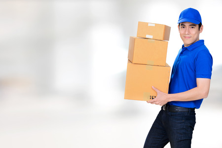 Smiling friendly delivery man carrying parcel boxes on blur white background 스톡 콘텐츠