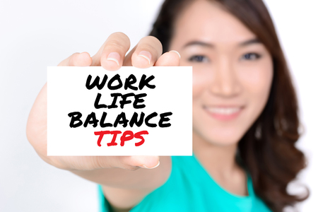 WORK LIFE BALANCE TIPS message on the card shown by a woman