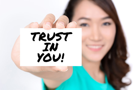 trustworthiness: TRUST IN YOU!, message on the card shown by a woman