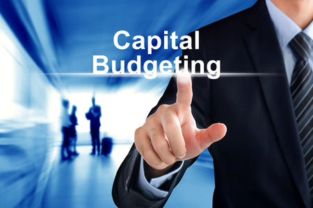 capital: Businessman hand touching Capital Budgeting text on virtual screen