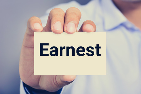 earnest: Earnest word on the card shown by a man, vintage tone Stock Photo
