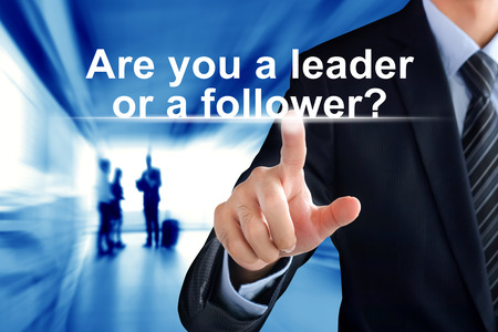 follower: Businessman hand touching Are you a leader or follower? message on virtual screen