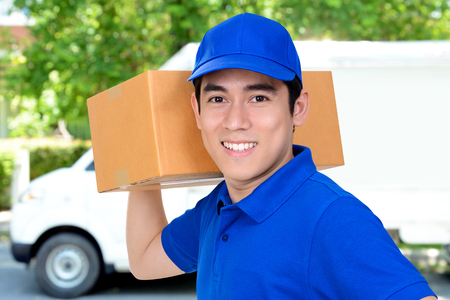 parcel: Smiling friendly delivery man carrying parcel box Stock Photo