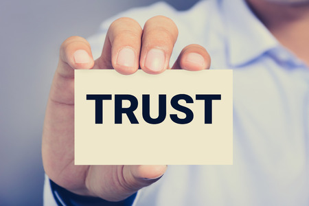 trustworthiness: TRUST word on the card shown by a man, vintage tone Stock Photo