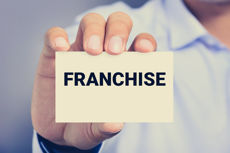 franchising: FRANCHISE word on the card shown by a man, vintage tone