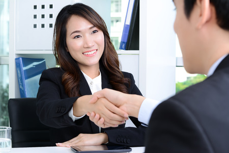 asian businesswoman: Asian businesswoman making handshake with a businessman in the office