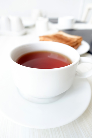taza de té: Té caliente en taza blanca con tostada borrosa sobre la mesa como fondo, concepto de desayuno - enfoque suave