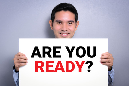 prepare: ARE YOU READY? message on white cardboard held by smiling man