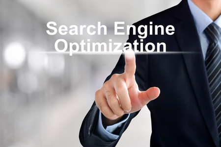 Businessman hand touching Search Engine Optimization (or SEO) text on virtual screen