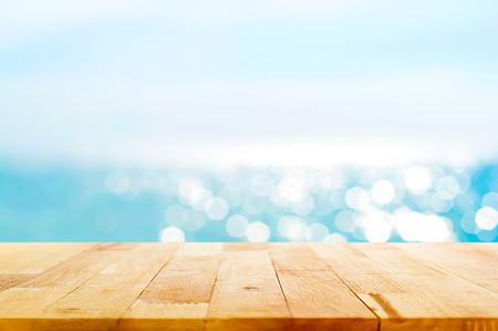 Houten tafelblad op onscherpte zomer blauwe zee en lucht achtergrond - kan worden gebruikt voor weergave of montering uw producten