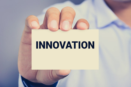 innovation word: INNOVATION word on the card shown by a man Stock Photo