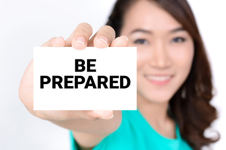 be prepared: BE PREPARED, message on the card shown by a woman Stock Photo