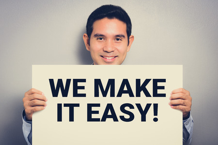 WE MAKE IT EASY! message on white cardboard shown by smiling man