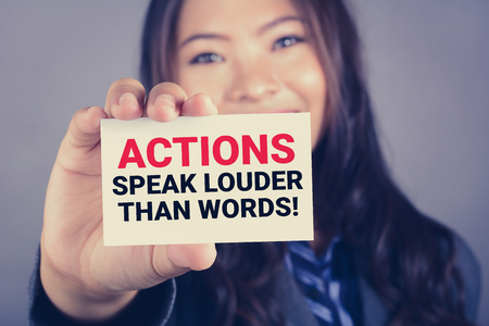 ACTIONS SPEAK LOUDER THAN WORDS, message on the card shown by a woman Stock Photo