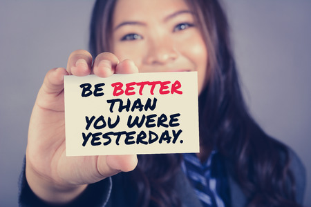 yesterday: BE BETTER THAN YOU WERE YESTERDAY, message on the card shown by a businesswoman Stock Photo