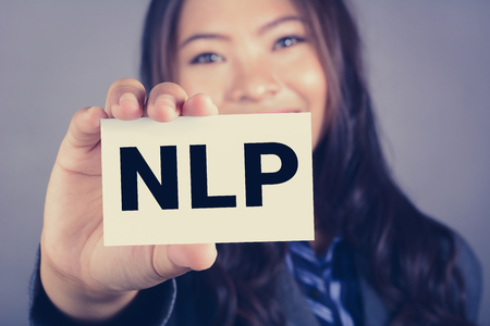 linguistic: NLP letters (or Neuro Linguistic Programming) on the card shown by a woman, vintage tone