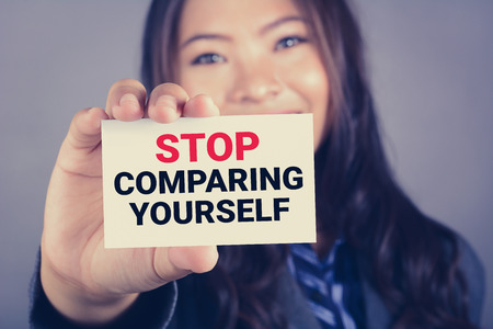 comparing: STOP COMPARING YOURSELF, message on the card shown by a woman, vintage tone