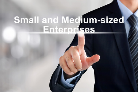 enterprises: Businessman hand touching Small and Medium-sized Enterprises (or SME) sign on virtual screen Stock Photo