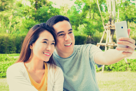 young asian: Young Asian couple taking selfie in the park, vintage tone Stock Photo