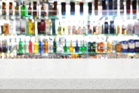 bar top: White stone bar top on blur colorful alcohol drink bottle background Stock Photo