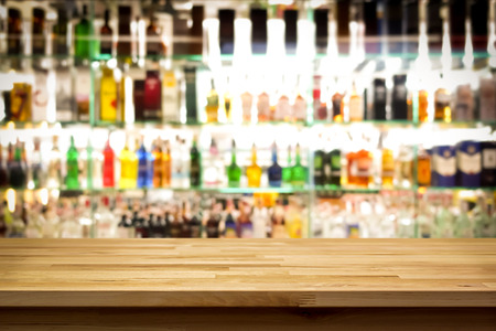 bar interior: Wood bar top on blur colorful alcohol drink bottle background