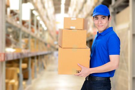 livraison Sourire homme portant des boîtes sur entrepôt de flou fond Banque d'images