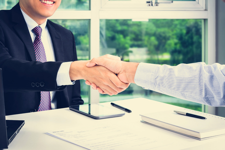 handclasp: Handshake of businessmen in the office - making agreement and dealing concepts
