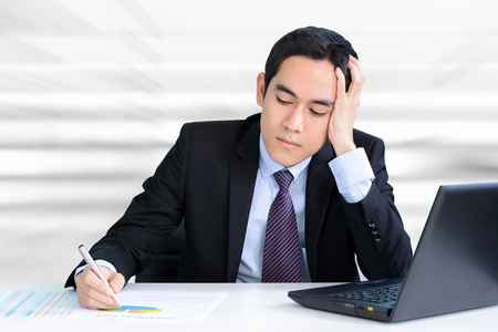 unsatisfied: Stressed businessman working at the table with hand on his head Stock Photo