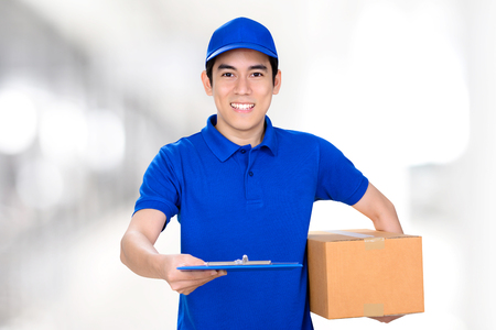 delivery box: Smiling delivery man giving clipboard while holding box with another hand