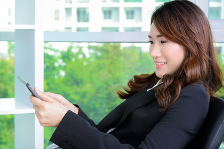 asian businesswoman: Young Asian businesswoman using  tablet computer while sitting in the office Stock Photo