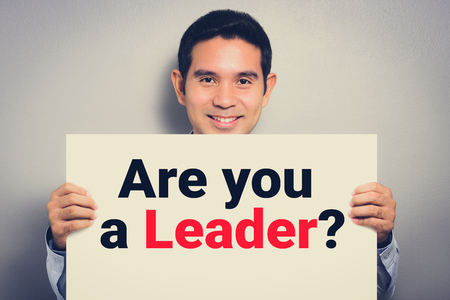ARE YOU LEADER? message on white cardboard held by smiling man Stock Photo