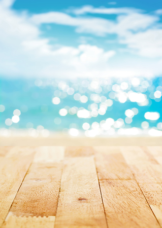 Wood table top on blur summer beach and sunny sky background - can be used for display or montage your products Stock Photo