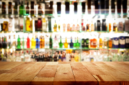 bar top: Wood bar top on blur colorful alcohol drink bottle background - can be used for display or montage your products Stock Photo