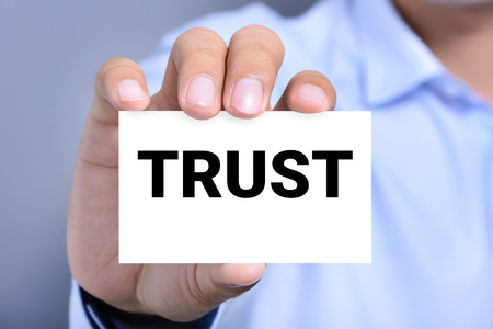 trustworthiness: TRUST word on the card shown by a man Stock Photo