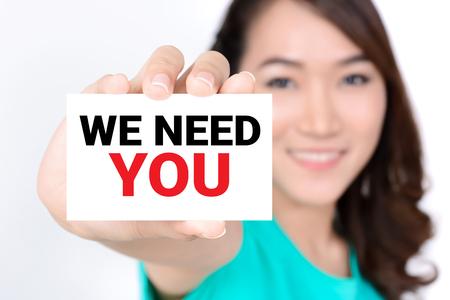 Abbiamo bisogno di te, messaggio sulla carta mostrato da una donna Archivio Fotografico