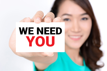 WE NEED YOU, message on the card shown by a woman 版權商用圖片